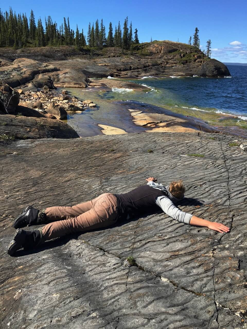 A picture of a student lying face down on a bed of rocks in a starfish position outside Great Slave Lake, with a rock hills and tall green trees in the background