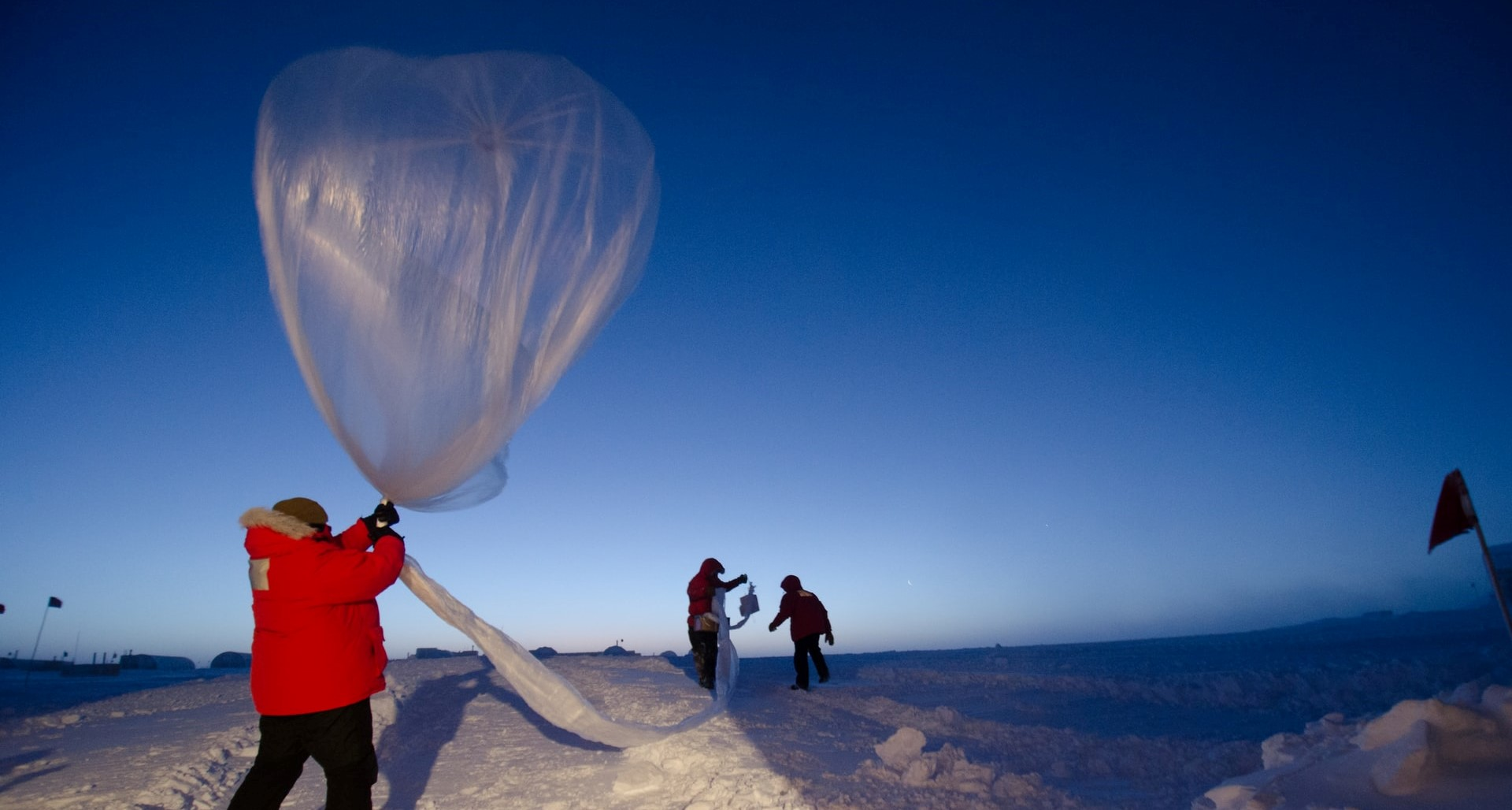 a person in the snow holding a weather balloon