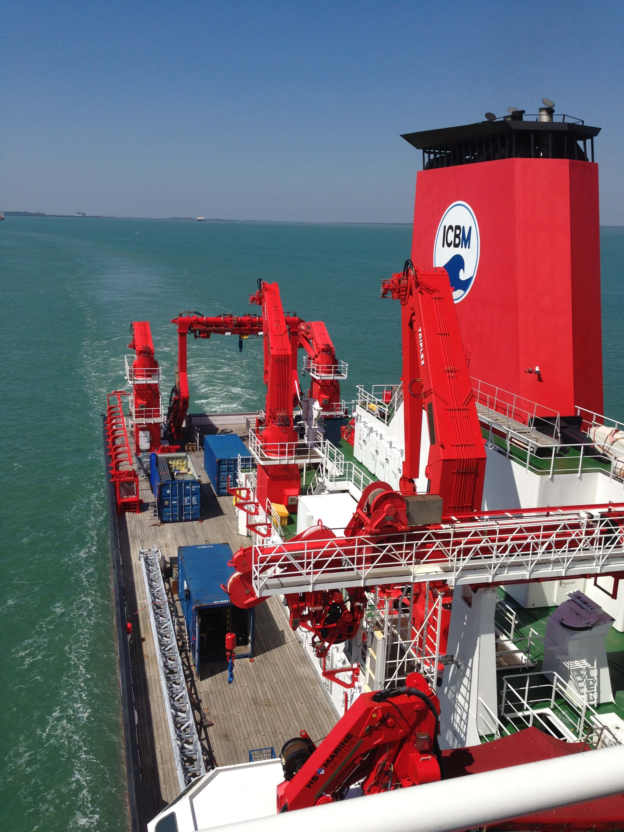 A large ship with numerous red cranes, with the logo