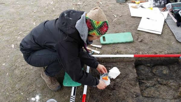 As student crouched over an archaeological site