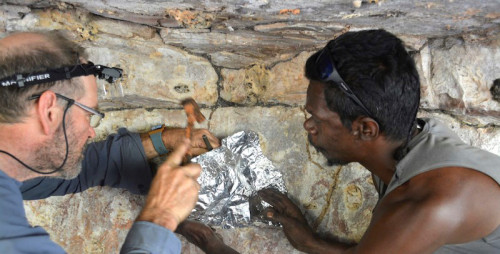 two people looking at rock paintings, one has a headtorch on and is hammering something into foil