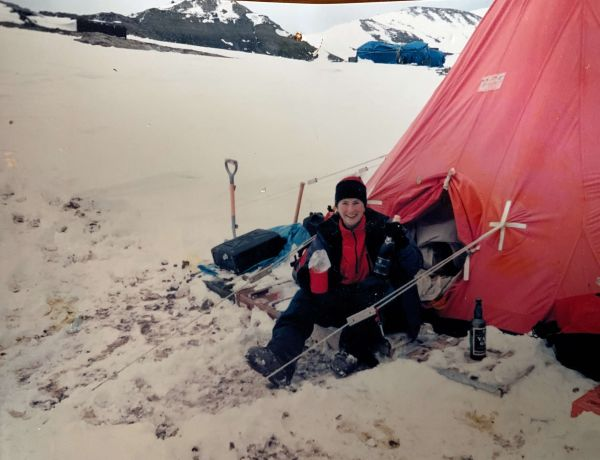 A researcher in Antarctica, sat next to a red tent, sitting on snow, smiling and wearing a black jacket and beanie, as well as a red jumper