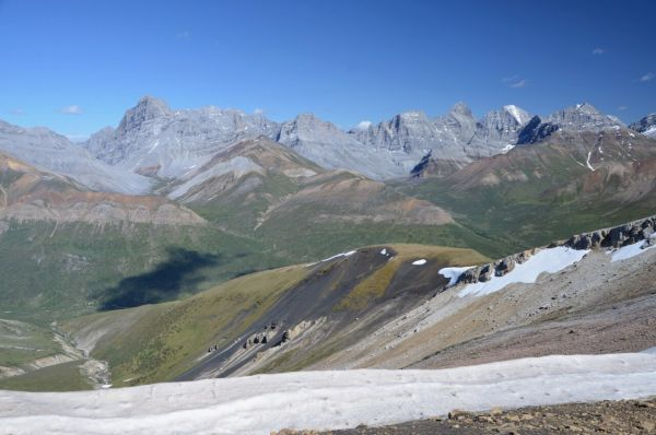 A picture of a valley of hills and mountains, covered largely in gravel in shades of brown and red, with larger grey mountains in the background, some semi-snow capped